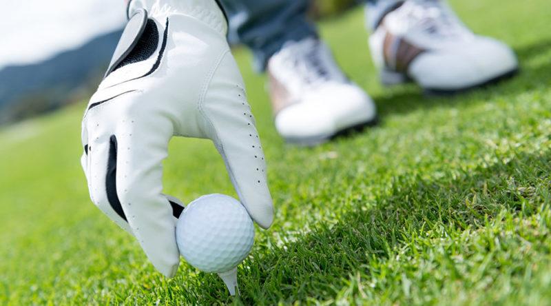 Man placing golf ball at the tee box