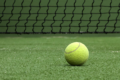 Tennis ball on synthetic grass of paddle court.