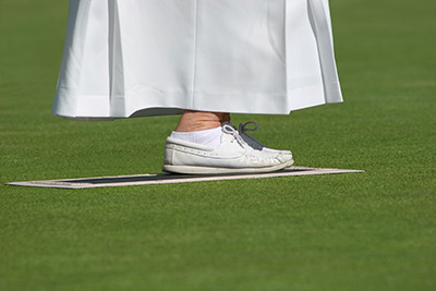 Ankles and feet of an elderly female wearing a long white skirt and white lawn bowling shoes, standing on a mat on a lawned area.