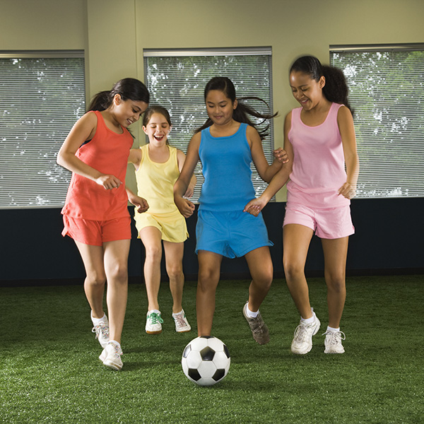 Four multiethnic girls playing soccer and laughing in indoor gym.