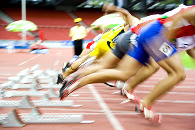 Image of 100 meters athletes at the starting block with intentional blurring.